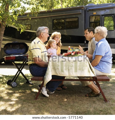 Three generation Caucasian family seated at picnic table in front of recreational vehicle talking.