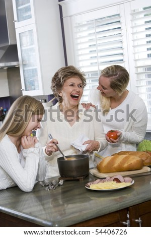 Three generation family in kitchen serving lunch, talking and laughing