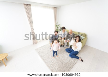 Three-generation family playing with dog stock photo