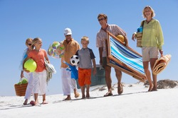 Three generation family walking on sandy summer vacation beach carrying deckchair bags towels and balls