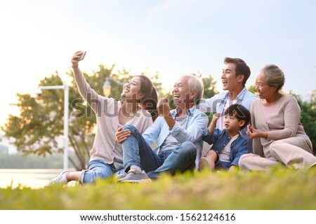 three generation happy asian family sitting on grass taking a selfie using mobile phone outdoors in park Stockfoto ©