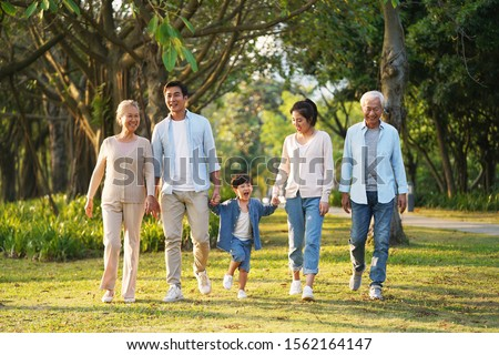 three generation happy asian family walking outdoors in park Stockfoto ©