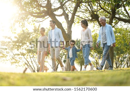 three generation happy asian family walking outdoors in park