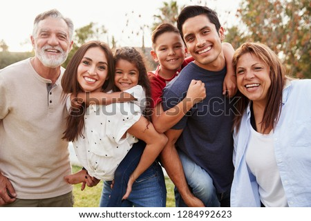 Three generation Hispanic family standing in the park, smiling to camera, selective focus