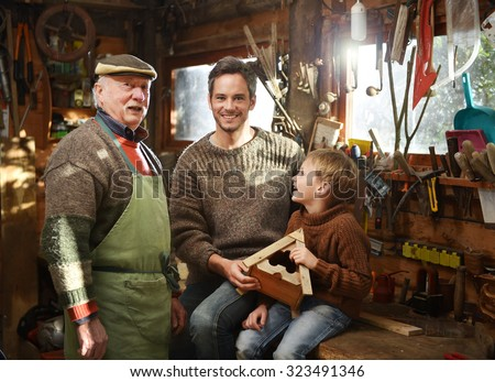 Three generations - father, grandfather and son are working on a wooden bird house. They are in the grandfather workshop, he is wearing a green apron and several tools are hanging from the ceiling