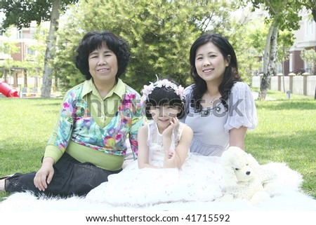 three generations in the family sitting on the grassland and having fun