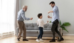 Three generations of active men dancing in living room little boy enjoy time with elderly grandfather and young father, concept of warm relations, understanding, best friends, intergenerational family