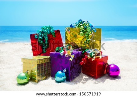 Three gift boxes and two gift bags with christmas balls on sandy beach in sunny day- holiday concept