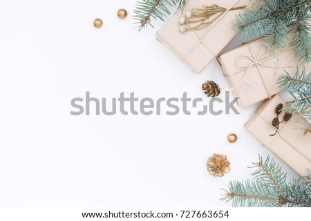 Three gift boxes, Christmas decorations, spruce branches and pine cones on white background. Top view, holiday composition.