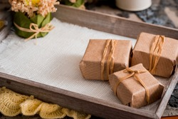 Three gift boxes in a kraft wrapper on a gray concrete background on a wooden table. place for your inscription