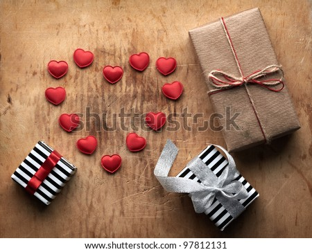 Three gift boxes with small hearts in shape of the heart. On old wooden background.