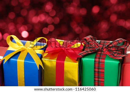 Three gifts on red blurry lights background.  Lining up colorful gifts.