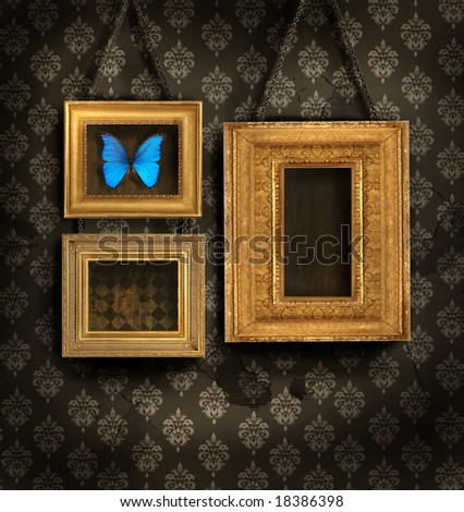 Three gilded frames on antique wallpaper background
