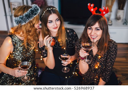 Three girl at a home Christmas party, one girl whispering something to the other, looking at the third girl. #526968937