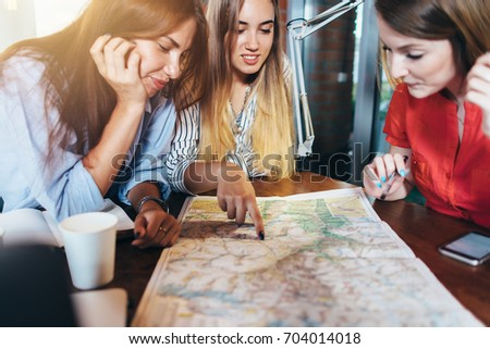 Three girlfriends planning their vacation sitting at table around map choosing the destination #704014018