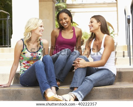 Three Girlfriends Sitting On Steps Of Building - stock photo