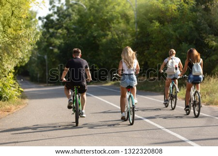 three girls and one guy ride bicycles outdoors, outdoor activities, lifestyle, concept of sport and youth