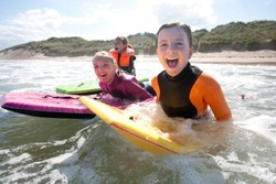 Three girls are smiling for the camera as they bodyboard in the sea together.