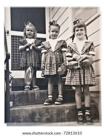 Three girls, cousins, dressed alike, at a birthday party posing for a picture on the front steps.