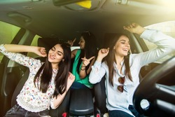 Three girls driving in a car dancing and having fun in city street