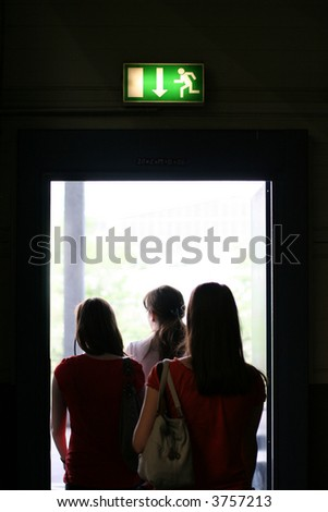 Three girls exit the building on exit door. Exit symbol