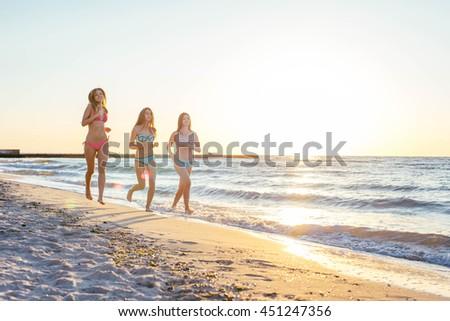 three girls having fun on beach, friends on beach in sunset light #451247356