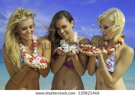 three girls in bikinis at a hawaii beach with flower lei