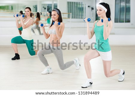 Three girls in fitness club workout with dumbbells