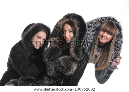 Three girls in fur coats on a white background