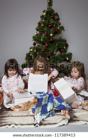 Three girls in pajamas sitting under the Christmas tree with gifts in their hands