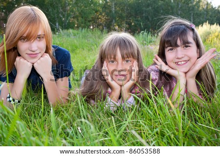 Three girls lying on meadow green grass smiling at camera - stock photo