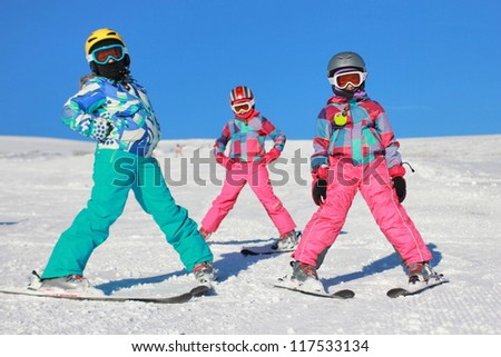 Three girls on the snow with ski equipment