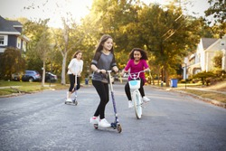 Three girls riding down the street on scooters and a bike