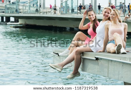 Three girls siting and chatting on seaside esplanade on summertime in Barselona at summertime #1187319538