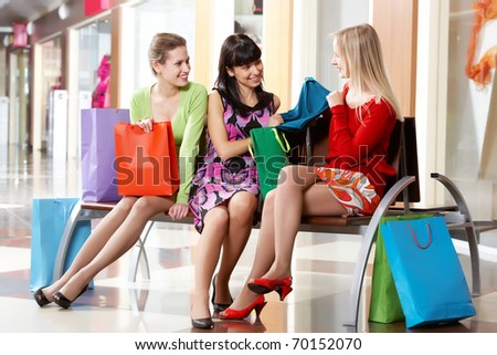 Three girls sitting in shopping mall and showing new clothing