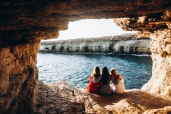 Three girls sitting in the sea cave shot from the back with amazing view of the bay. Amazing sea caves. Beautiful unusual places of the world. Girls traveling together during summer holidays.