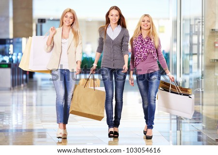 Three girls with shopping bags in store