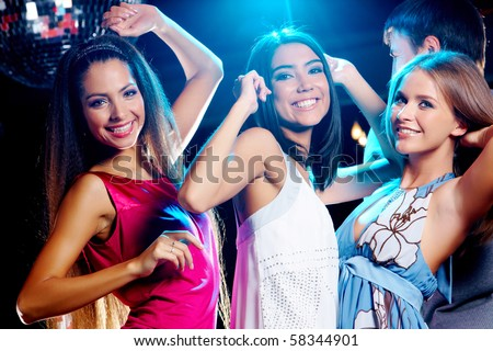 Three glamorous girls enjoying themselves while dancing in night club