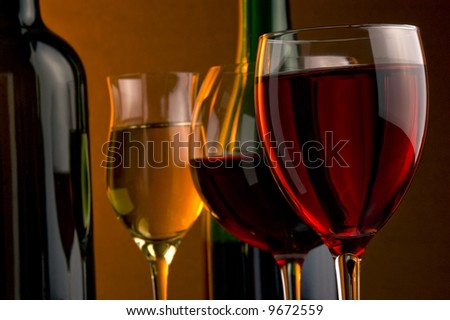 three glass and two bottles red, white and rose wine