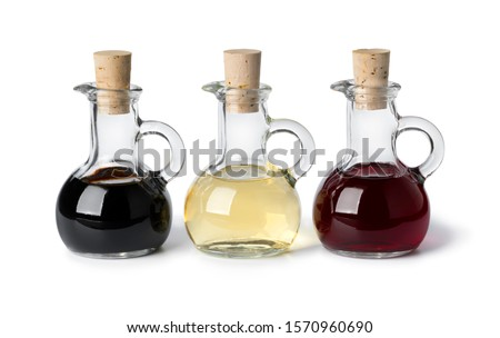 Three glass bottles with different types of vinegar isolated on white background Foto stock ©