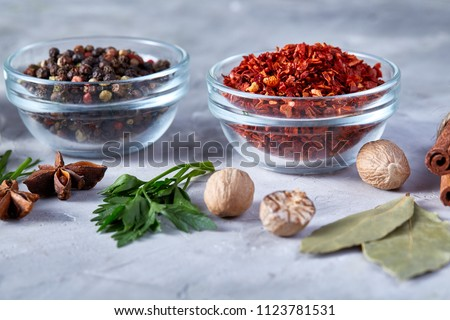 Three glass bowls with spices arranged in rows on white textured background, view from above.