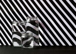 Three glass jars placed together of different sizes with water. Background of white and black lines in diagonal, making visible the effect of the refraction of water.