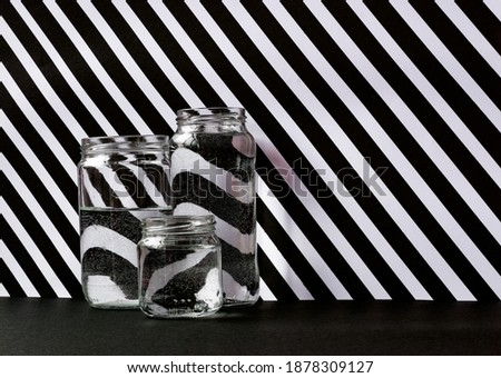 Photo of  Three glass jars placed together of different sizes with water. Background of white and black lines in diagonal, making visible the effect of the refraction of water.