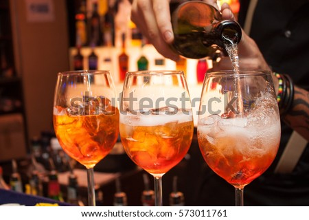 three glasses of cocktails on the bar. bartender pours a glass of sparkling wine with Aperol. #573011761