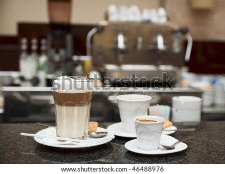 Three glasses of coffee, cafe equipment in blurred backgound
