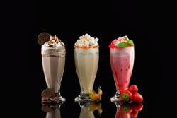 Three glasses of colorful milkshake cocktails - chocolate, strawberry and vanilla decorated with fresh berries and mint isolated at black background.