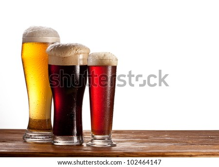Three glasses of different beers on a wooden table. Isolated on white.