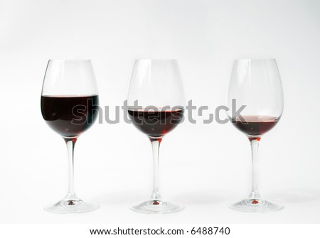 three glasses of red wine filled in different levels. Full, half full, almost empty.
