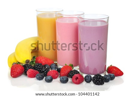 Three glasses of  smoothies with different berries and bananas