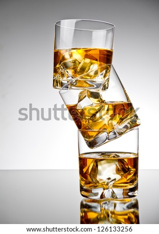 Three glasses of whiskey on the rocks, one on top of the other